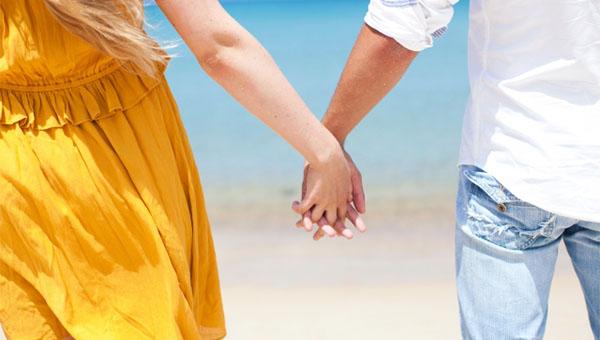 海辺で手をつなぐ夫婦
